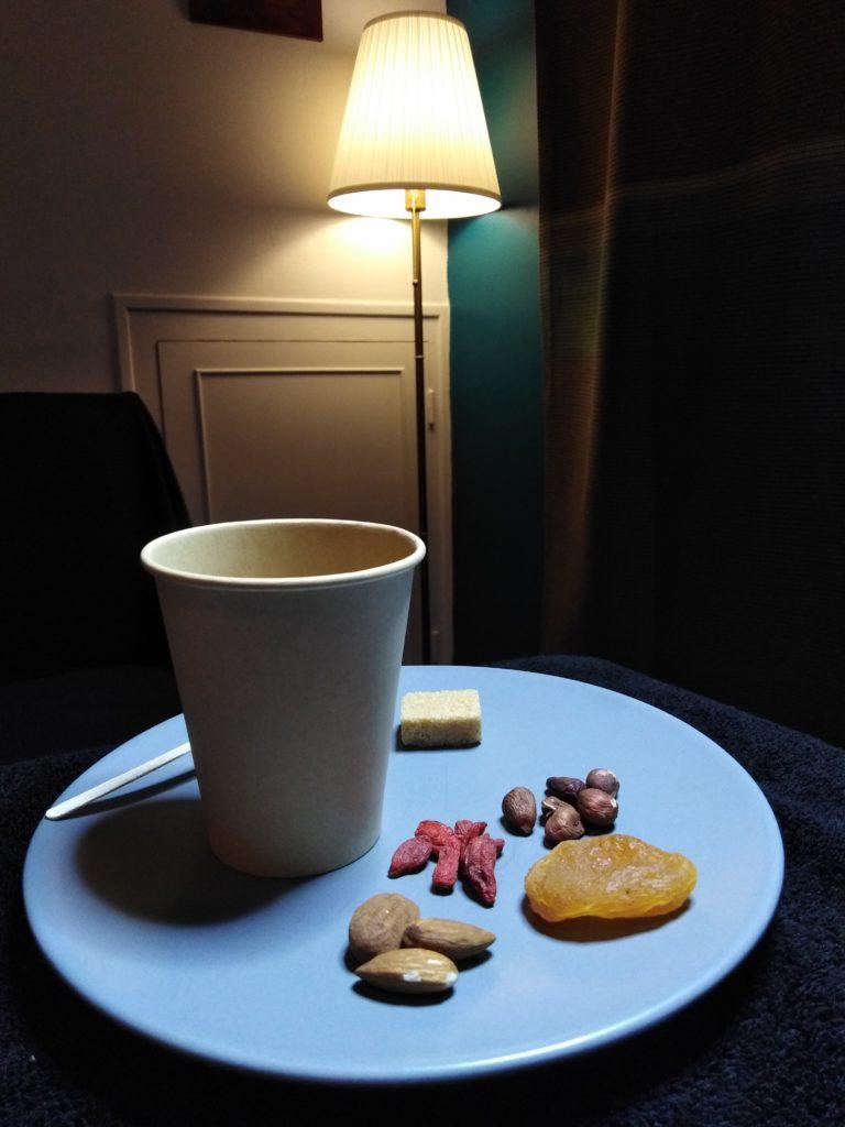 Intérieur cosy de la salle de soins.Collation sur une assiette à dessert bleue. Tisane dans un gobelet en carton beige,fruits secs (abricot, amandes, noisettes, baies de gogi). Une lampe sur pied allumée dans le coin de la pièce met en valeur les boiseries peintes.