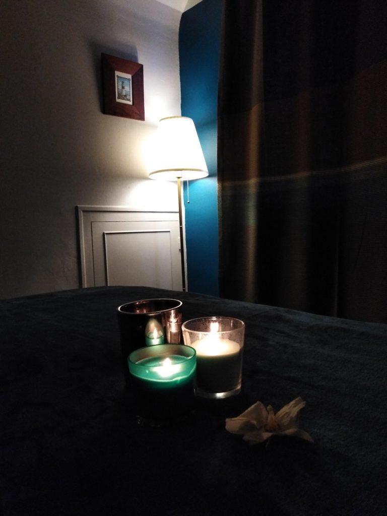 Bout de table de soins sur lequel sont posées des bougies allumées ainsi qu'une fleur d'orchidée. la pièce est plongée dans une atmosphère extrêmement tamisée, propice à la relaxation.