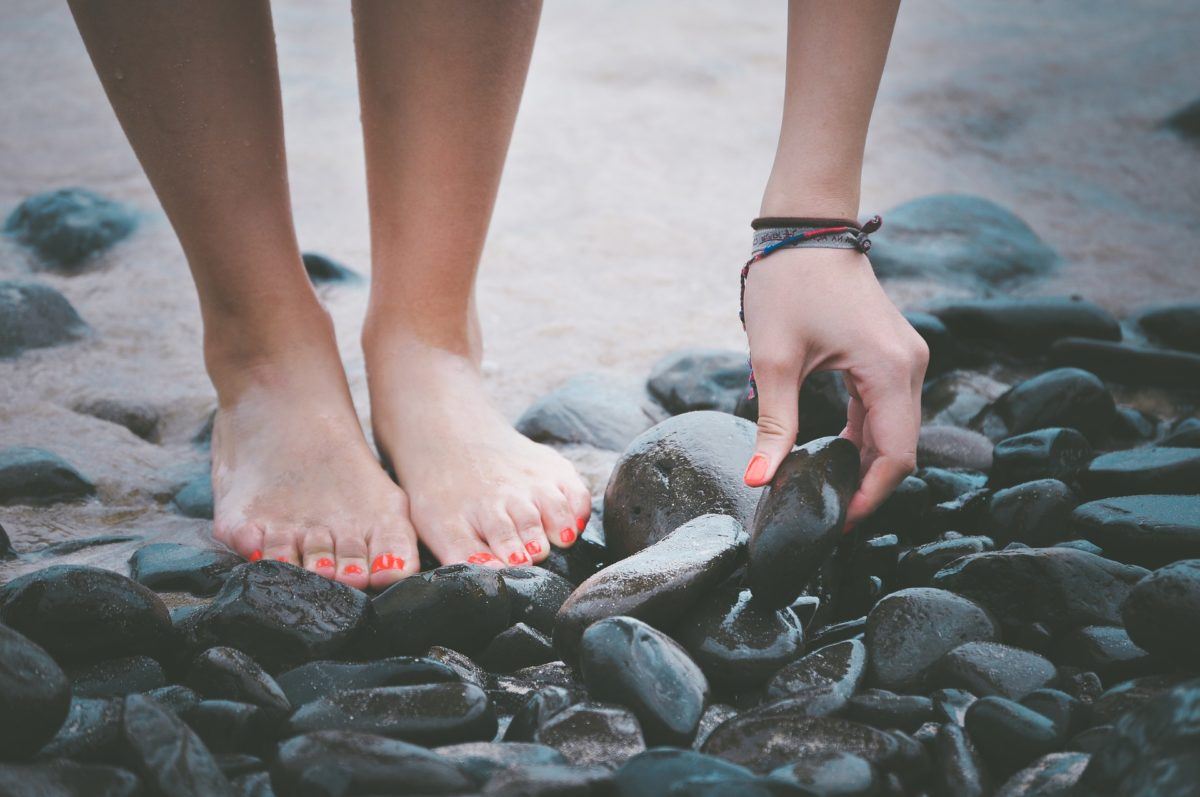 Pieds et mains d'une jeune femme qui se penche pour ramasser un galet sur une plage.