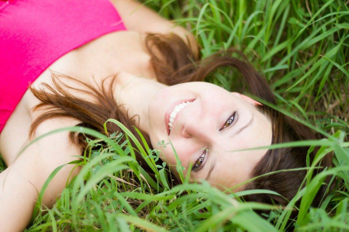 Jeune femme souriante, allongée sur des herbes hautes.