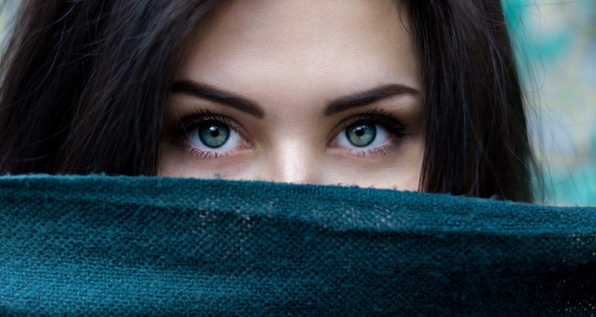 viasge en gros plan d'une jeune femme aux beaux yeux bleus et dont le bas du visage est dissimulé par une étoffe laineuse bleu pétrôle.