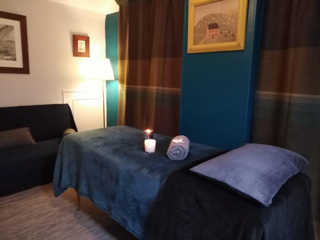 Institut de beauté bio. Photo de la salle de soins présentant une table de massage sur laquelle sont posées des bougies allumées. Des cadres sont accrochés aux mur. La salle dispose d'un canapé et de deux fenêtres occultées par d'épais rideaux. C'est un intérieur cosy!