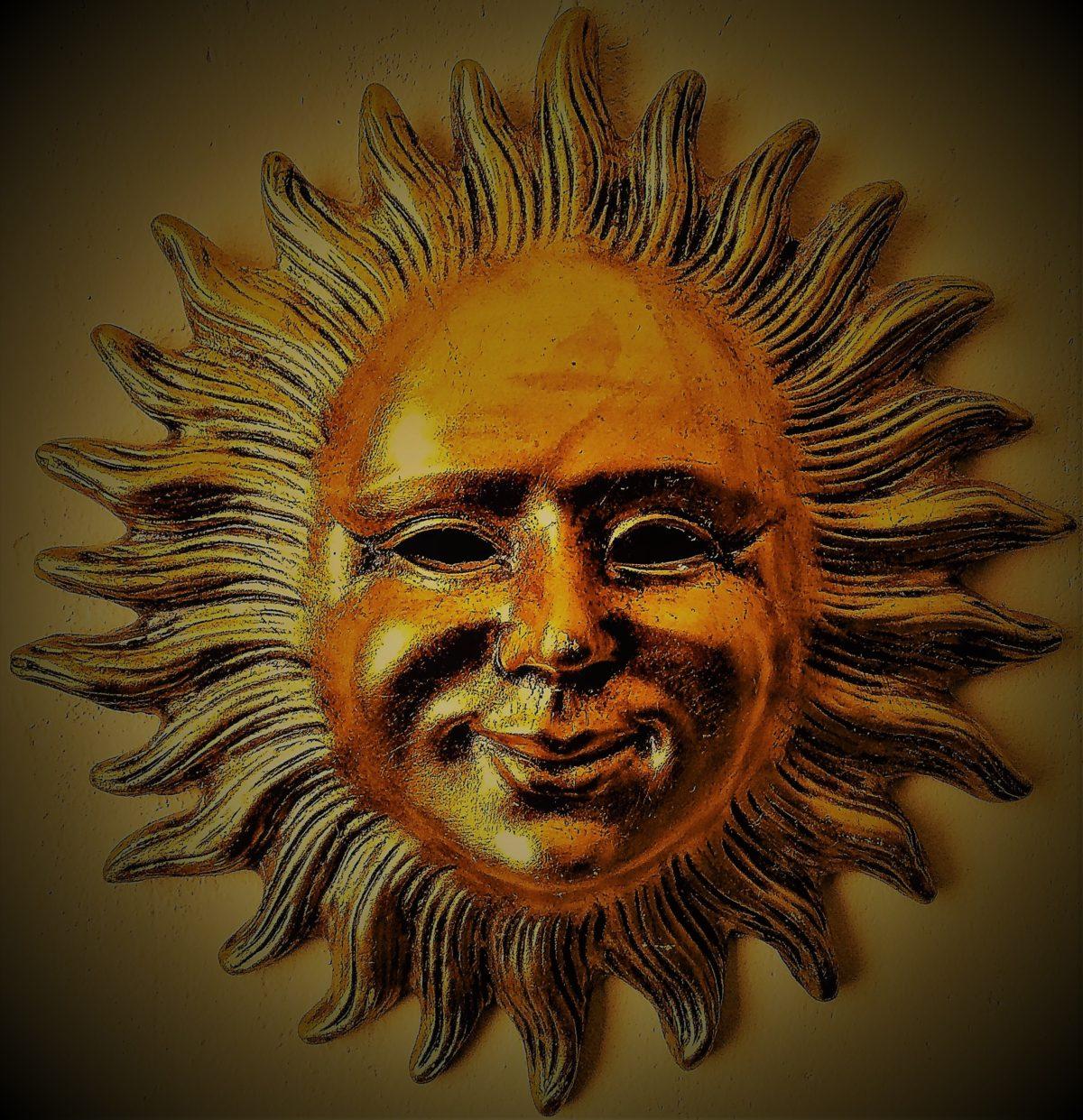 Soleil vénitien doré figurant un visage humain souriant et bienveillant.